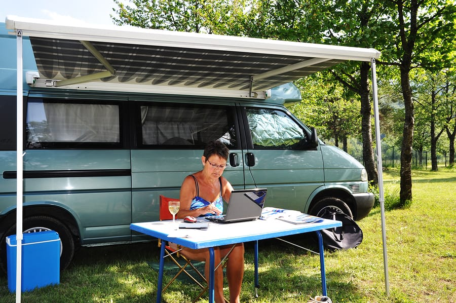 Lady Using Computer Next To Campervan thanks to the best Portable Generators For Camping & RVs